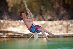 Menino principal vermelho que balanç na corda Imagem de Stock Royalty Free