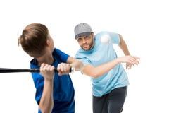 Menino pronto para bater a bola durante um jogo de basebol Pai e criança que jogam o basebol Fotografia de Stock