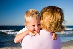 Menino que abraça a matriz na praia Fotografia de Stock Royalty Free