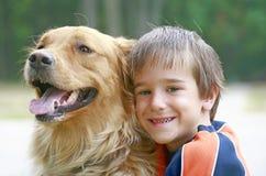 Menino que abraça o cão Fotografia de Stock Royalty Free