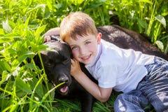 Menino que abraça um cão grande em um ajuste exterior Foto de Stock Royalty Free