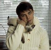 Menino que abraça um gato cinzento bonito Fotos de Stock