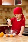 Menino que ajuda na cozinha com torta do cozimento Fotos de Stock Royalty Free
