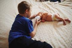 Menino que alimenta o bebê recém-nascido com a garrafa do leite fotografia de stock royalty free