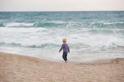 Menino que anda ao longo do litoral Fotografia de Stock Royalty Free