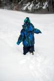 Menino que anda na neve profunda Fotografia de Stock