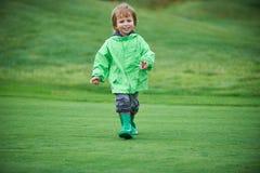 Menino que anda o campo de golfe Foto de Stock Royalty Free