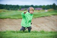 Menino que anda o campo de golfe Fotografia de Stock