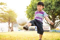 Menino que aprende a bola do pontapé no parque na noite fotografia de stock royalty free