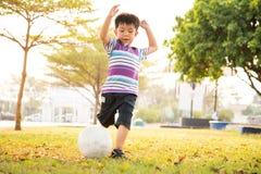 Menino que aprende a bola do pontapé no parque na noite imagem de stock royalty free