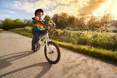Menino que aprende montar sua bicicleta fotos de stock