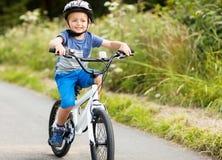 Menino que aprende montar sua bicicleta foto de stock