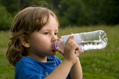 Menino que bebe a água engarrafada. Imagem de Stock Royalty Free