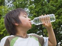Menino que bebe a água mineral Imagens de Stock Royalty Free