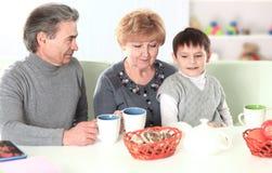 Menino que bebe o chocolate quente e avós felizes foto de stock royalty free