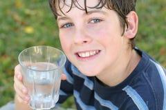 Menino que bebe um vidro da água Foto de Stock Royalty Free