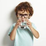 Menino que bebe um vidro da água imagens de stock