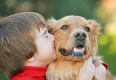 Menino que beija o cão Imagens de Stock