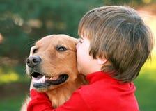 Menino que beija o cão Fotos de Stock Royalty Free