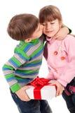 Menino que beija uma caixa de presente da terra arrendada da menina Fotografia de Stock Royalty Free