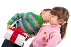 Menino que beija uma caixa de presente da terra arrendada da menina Imagem de Stock Royalty Free