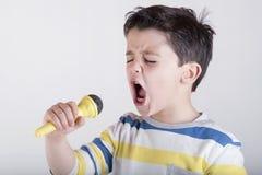 Menino que canta ao microfone imagem de stock