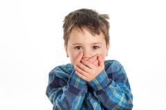 Menino que cobre sua boca Foto de Stock Royalty Free