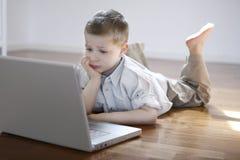 Menino que coloc no assoalho com computador portátil Foto de Stock Royalty Free