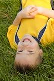 Menino que coloca na grama Fotografia de Stock