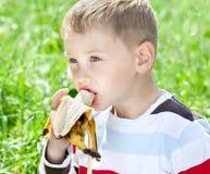 Menino que come a banana Imagens de Stock