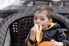 Menino que come a banana Foto de Stock Royalty Free