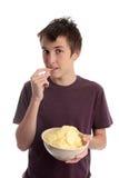 Menino que come batatas fritas da batata Foto de Stock Royalty Free