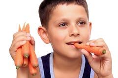Menino que come a cenoura Fotografia de Stock