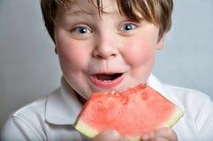 Menino que come a melancia Fotos de Stock