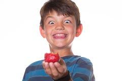 Menino que come a morango com uma cara pateta Fotografia de Stock Royalty Free