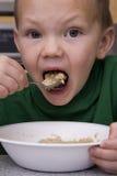 Menino que come a mordida grande do oatmeal Imagem de Stock Royalty Free