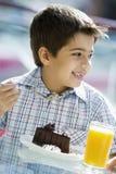 Menino que come o bolo de chocolate no café Fotos de Stock