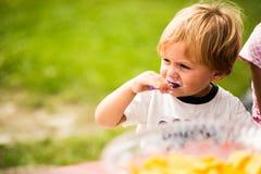 Menino que come o bolo em uma festa de anos exterior Imagem de Stock