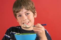 Menino que come o cereal fotografia de stock royalty free