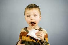 Menino que come o chocolate Fotografia de Stock