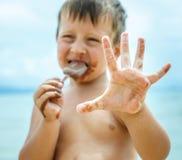 Menino que come o gelado de chocolate no mar Fotografia de Stock Royalty Free