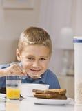 Menino que come o pequeno almoço Foto de Stock