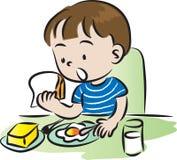 Menino que come o pequeno almoço Fotografia de Stock