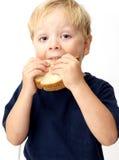 Menino que come o sanduíche Imagem de Stock