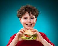 Menino que come o sanduíche grande Imagens de Stock