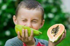 Menino que come a papaia Imagem de Stock Royalty Free
