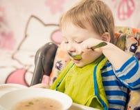 Menino que come a sopa Fotos de Stock