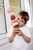 Menino que come um cone de gelado alto Fotos de Stock Royalty Free