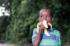 Menino que come um fruto Fotos de Stock