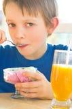 Menino que come um gelado saboroso Fotografia de Stock